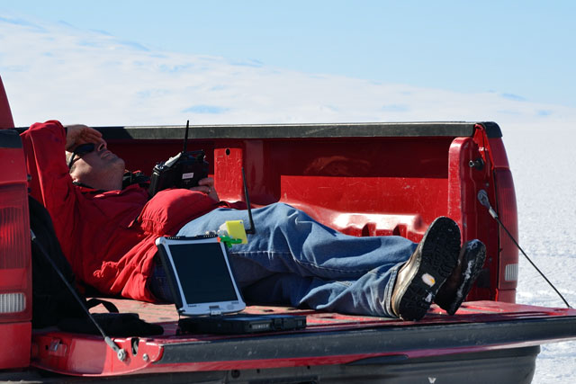 Person reclines in pickup truck bed.
