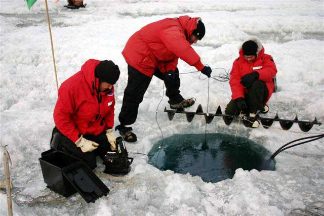 People gather around a hole in the ice.