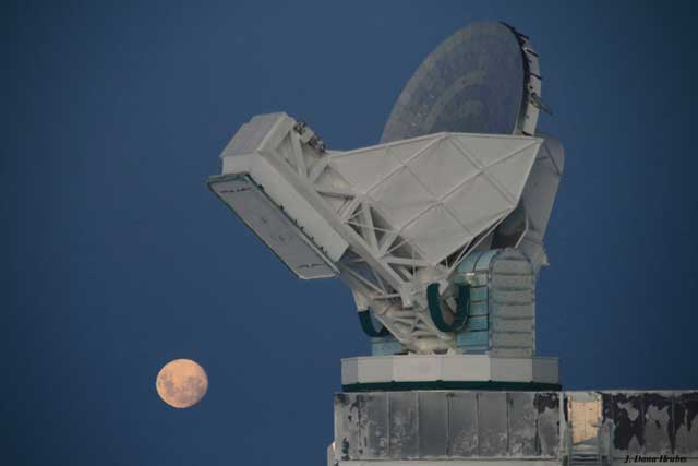 Full moon shines behind telescope.