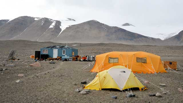 Tents and small buildings sit in front of barren mountain.