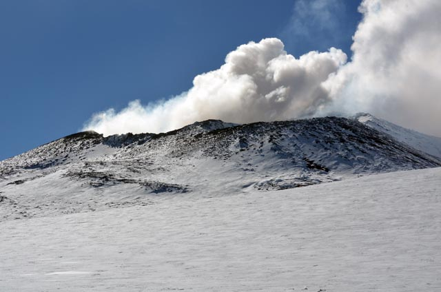 Smoke rises from mouth of volcano.