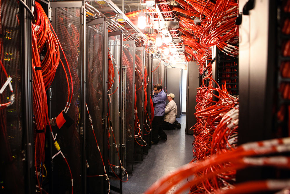 People work in a computer server room with lots of cables.