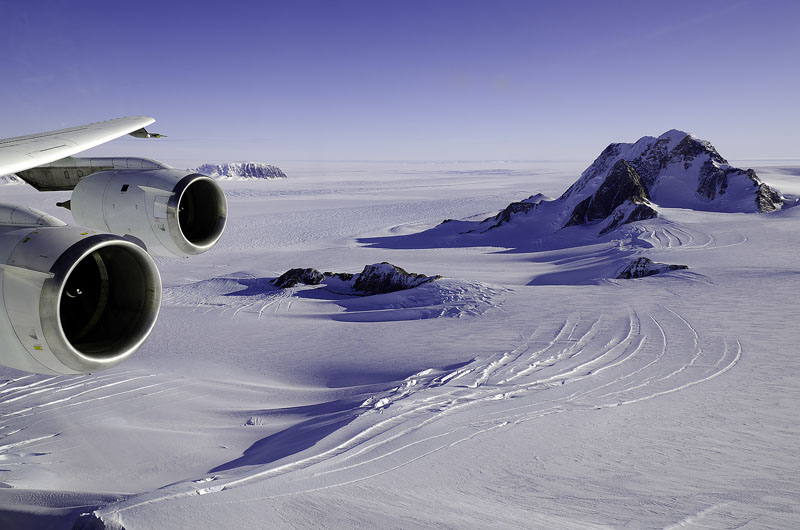 A plane wing is visible of plane flying over icy landscape.