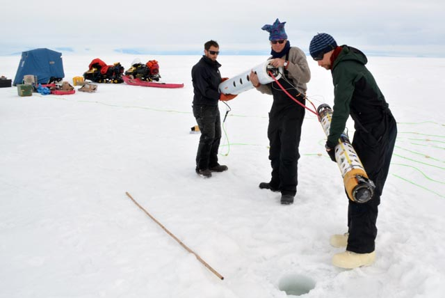 People carry instrument to an ice hole.