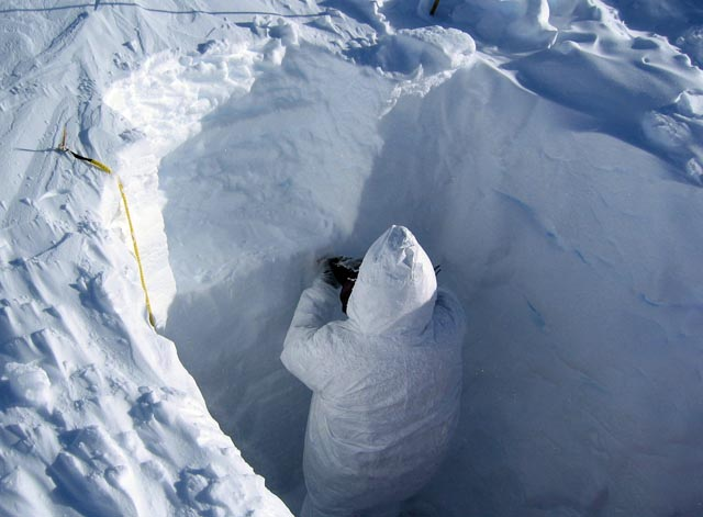 Person stand in snow pit.