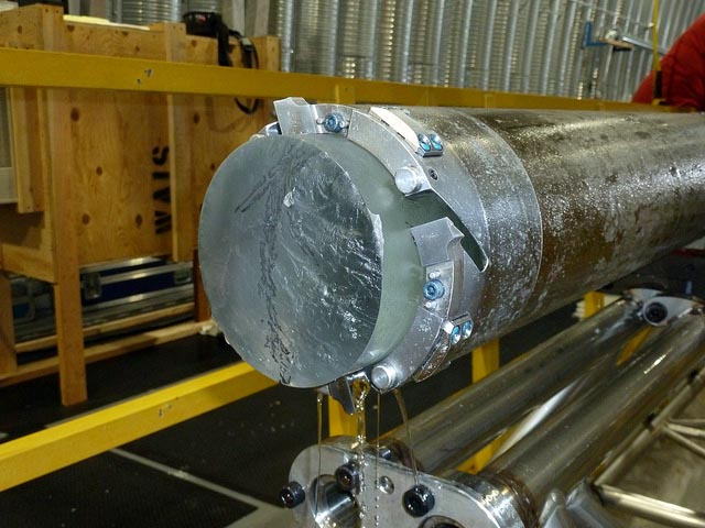 Ice core sticks out of metal barrel.