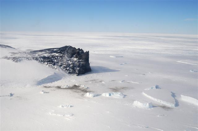 Large rock outcrop surrounded by ice.