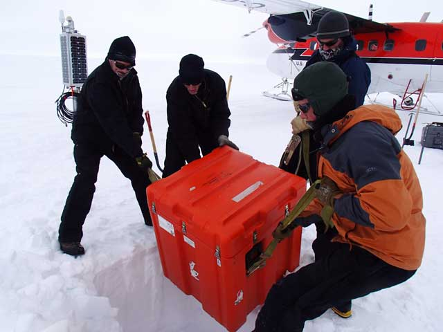 People lift a big orange box in cold weather.