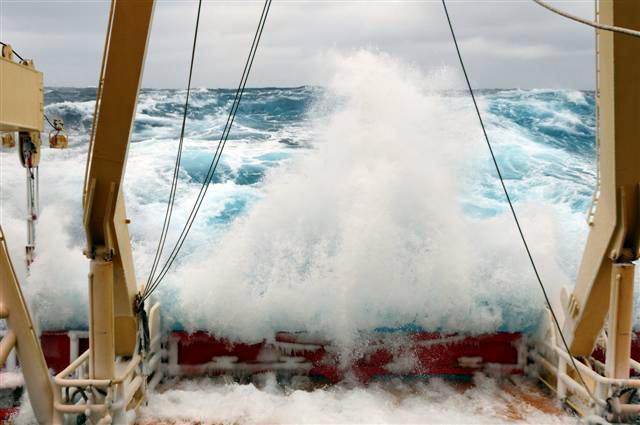 Waves crash over stern of ship.