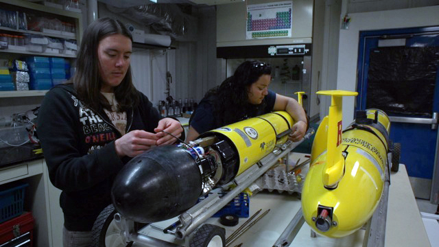 Two people assemble torpedo-shaped robots.