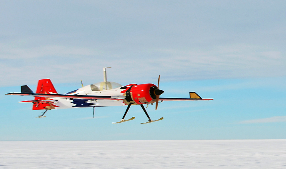 Small plane flies over snow.