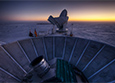 The sun sets behind BICEP2, foreground, and the South Pole Telescope at NSF's Amundsen-Scott South Pole Station