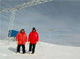 Scientists Jef Spaleta and Alexander Morris stand near the SuperDARN array at the South Pole Station.