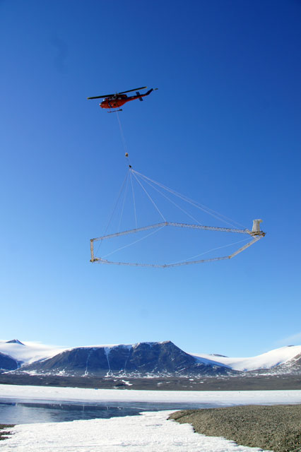 Helicopter carries large loop through icy landscape.