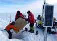 Scientists and engineers install a seismic station on the Ross Ice Shelf by snowmobile.