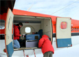 Personnel with the National Center for Airborne Laser Mapping install the laser-mapping instrument in a Twin Otter aircraft.