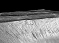 A 3D projection of satellite data showing the dark briny streaks of water flowing, also known as recurring slope lineae down the Walls of Garni Crater on Mars.