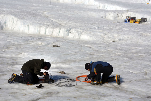 People set up equipment on ice.