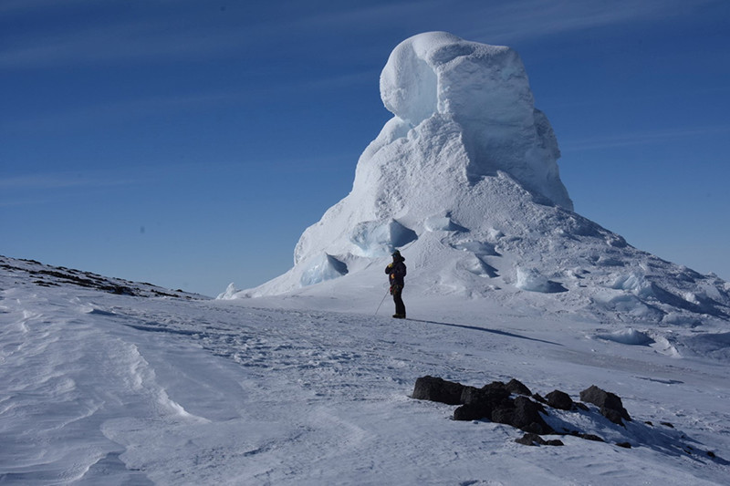 Mountaineer Tom Schaefer stands in front of a fumarole, an ice tower formed when water vapor refreezes into frozen tower