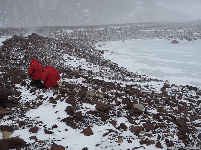 Jen Lamp and Kate Swanger collect rock samples along the headwall of the Mullins Glacier in inclement weather.