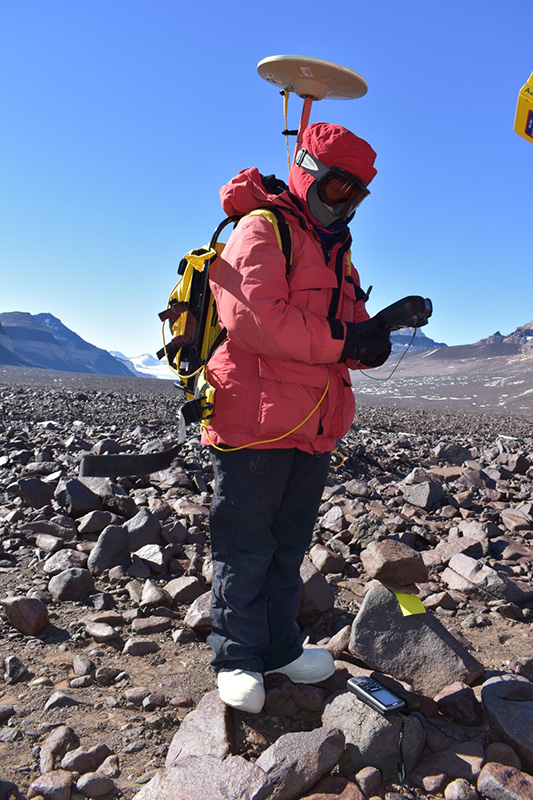 Kate Swanger hauls a GPS unit to get precise location data for each rock sample they collected.