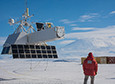 The GRIPS scientific payload hangs suspended over the frozen surface of McMurdo Station's Long Duration Balloon field as one of launch crew looks on.