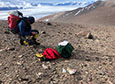 Mountaineer Geoff Schellens kneels and takes a GPS measurement where the team collected a soil sample, with the Transantarctic Mountains in the background.