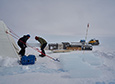 Tanner Kuhl (left) and John Higgins carry a recently recovered ice core out of the drill tent.