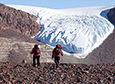 Researchers Allie Belter (left) and Gregory Balco hike towards the Shackleton Glacier spilling over a section of Roberts Massif.