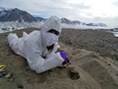 While wearing a sterile over suit to prevent contamination, Sarah Johnson collects samples of desiccated microbial from an ancient lake bed in Taylor Valley.