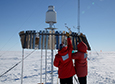 Carol Costanza (left) and Scott Landolt install a section of aluminum fins around the precipitation gauge at the Tall Tower site on the Ross Ice Shelf