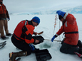 Benjamin Van Mooy (right) and Jamie Collins take water samples from under the ice in Arthur harbor