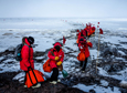 Student participants carry sampling equipment and cold weather gear to a sampling site near McMurdo Station