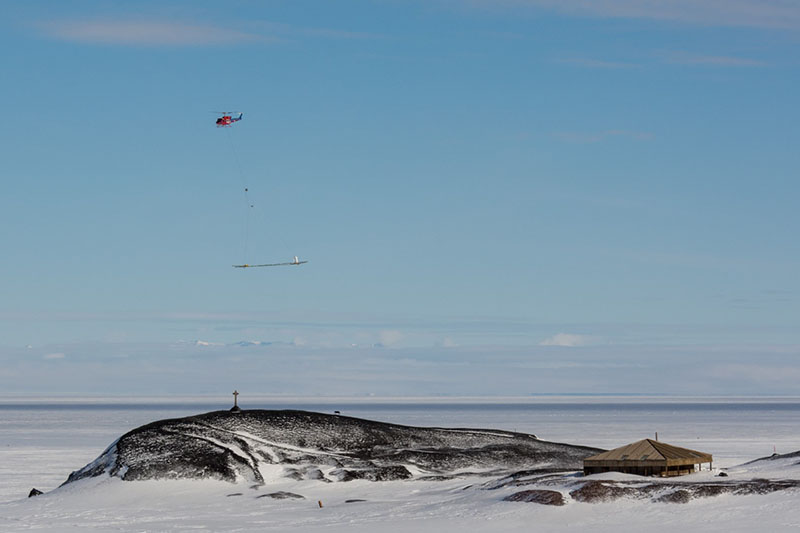 With SkyTEM slung underneath, a Bell 212 helicopter flies past the Discovery historic hut on Hut Point Peninsula