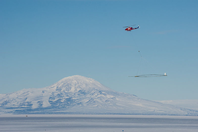 With SkyTEM in tow, a Bell 212 helicopter flies over the sea ice of McMurdo Sound on a practice run