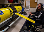 Katie Holmes works on a Slocum glider from the University of Alaska Fairbanks, used to monitor the oceanic conditions around Palmer Station.